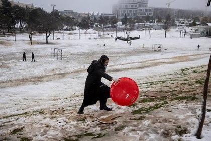 Un niño judío ultraortodoxo juega con la nieve en un parque en una mañana nevada en Jerusalén, el 18 de febrero de 2021. REUTERS / Ronen Zvulun