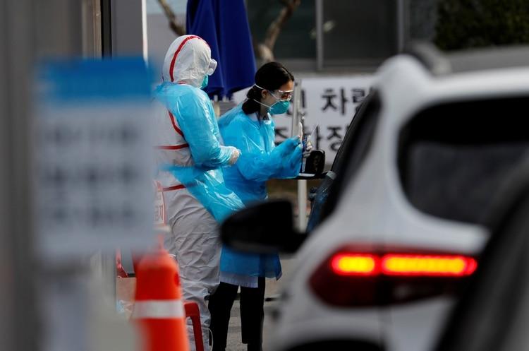 Un miembro del personal médico con equipo de protección se prepara para tomar muestras de un visitante en un auto en un centro de pruebas en Daegu, Corea del Sur, el 3 de marzo de 2020. (REUTERS/Kim Kyung-Hoon)