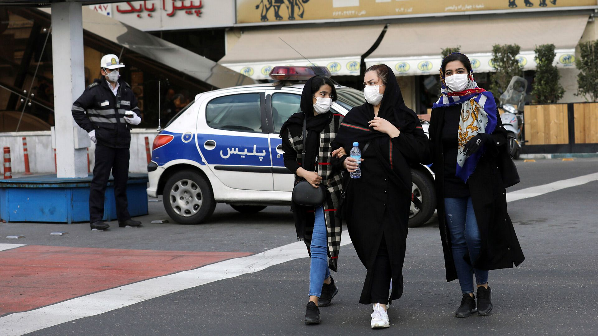 Un policía y unos peatones llevan máscaras para protegerse del Coronavirus, en el centro de Teherán (Foto AP/Ebrahim Noroozi)