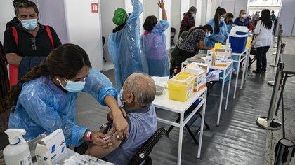 Un trabajador de la salud inocula a un anciano con una dosis de la vacuna contra el COVID-19 en un centro de inmunización instalado en el Estadio Bicentenario en Santiago de Chile