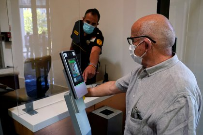 Un hombre revisa la temperatura de su cuerpo para ingresar al museo del Prado mientras se reabre al público bajo estrictas medidas de distancia social, en medio del brote de la enfermedad del coronavirus (REUTERS)