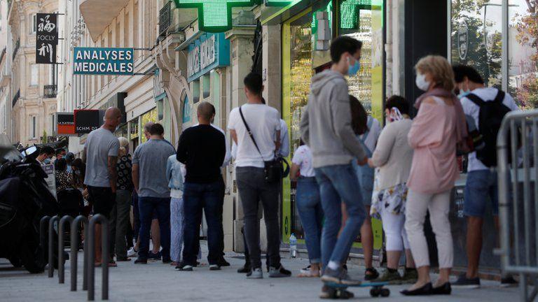 Gente haciendo fila en una farmacia de París