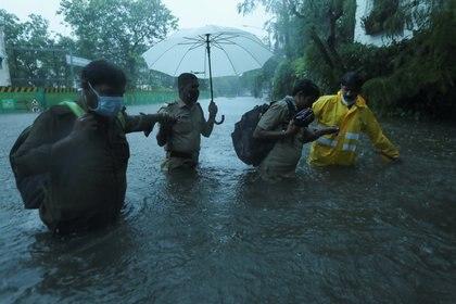 Personal de emergencia ayuda a cruzar una calle inundada en Bombay (Reuters)