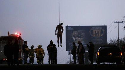 Un cuerpo mutilado cuelga de un puente en Tijuana, un típico ritual de venganza narco (AP)