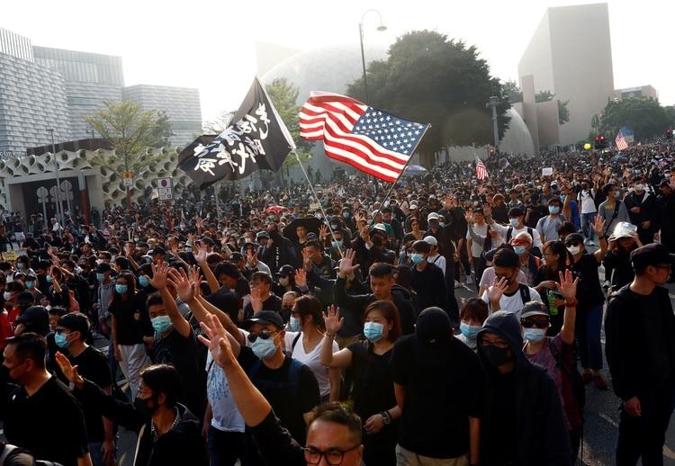 Los manifestantes antigubernamentales levantan la mano mientras asisten a la manifestación