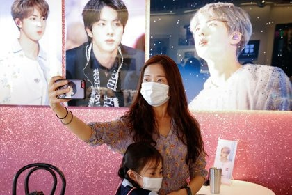 Foto del jueves de una fan del grupo de K-pop BTS sacándose una selfie en un bar en Seúl decorado con fotos de la banda.  Sep 24, 2020.    REUTERS/Heo Ran
