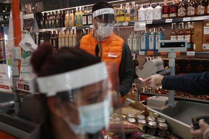 Alberto Rabal, cajero de un supermercado, lleva un escudo protector y una máscara facial mientras atiende a los clientes tras el brote de la enfermedad coronavirus (COVID-19) en Madrid, España, el 25 de abril de 2020 (Reuters)
