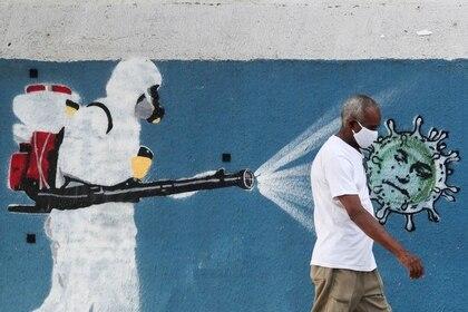 Un hombre camina junto a un graffiti que muestra a un limpiador con equipo de protección rociando con limpiador al virus de coronavirus con la cara del presidente de Brasil, Jair Bolsonaro, en medio del brote de COVID-19, en Río de Janeiro, Brasil, 12 de junio de 2020. REUTERS / Sergio Moraes