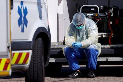 Un empleado sanitario descansa durante el traslado de pacientes de coronavirus a Alemania (Reuters)