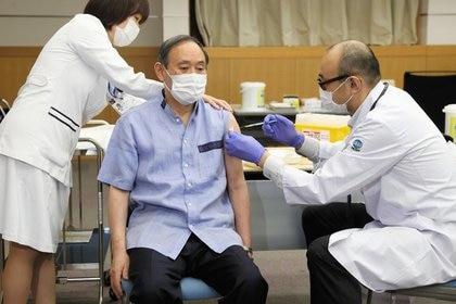 El primer ministro de Japón, Yoshihide Suga, recibe su primera dosis de la vacuna anti-COVID-19 de Pfizer-BioNtech en el Centro Nacional de Salud y Medicina Global en Tokio, Japón, 16 de marzo de 2021, REUTERS/Kyodo