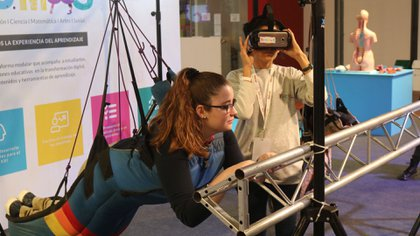Una joven se coloca un arnés y luego, con las gafas, simulará volar en ala delta