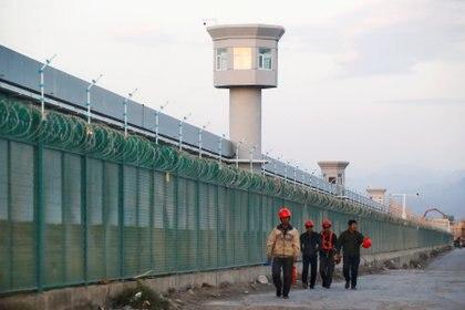 Trabajadores caminan junto a la valla perimetral de uno de los campos de concentración para los uigures en Xinjiang (REUTERS/Thomas Peter/Archivo)