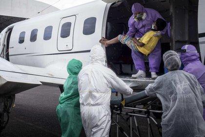 Paramédicos fueron registrados este viernes al recibir un niño de 10 años contagiado de COVID-19 y procedente de Santo Antonio del Iça, un municipio ubicado a casi 900 kilómetros de la capital estatal, en Manaos (Brasil). EFE/Raphael Alves