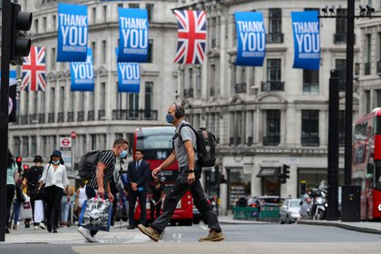People wearing protective masks walk at Oxford Circus, as the spread of the coronavirus disease (COVID-19) continues, in London, Britain July 24, 2020. REUTERS/Simon Dawson