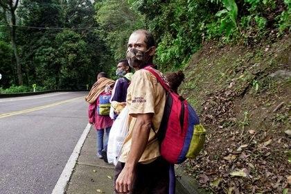 Migrantes venezolanos con máscaras faciales debido al brote de (COVID-19) caminan de regreso por las carreteras colombianas después de que los sectores económicos fueron reactivados, cerca a la ciudad de Bucaramanga, Colombia, 30 de octubre, 2020.