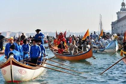 Los barcos decorados con juerguistas se mueven en el Gran Canal durante la regata de apertura del Carnaval de Venecia el 17 de febrero de 2019 (AFP)