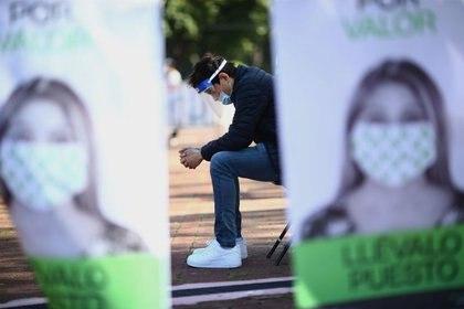 Un hombre lleva puestas una máscara y una careta protectora mientras espera afuera de un centro temporal para relizar pruebas para detección de coronavirus en Ciudad de México. 15 de octubre de 2020. REUTERS/Edgard Garrido