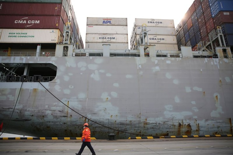 Un trabajador con una máscara facial pasa por delante de un buque de carga en una terminal de contenedores del puerto de Qingdao en la provincia de Shandong, China (REUTERS, Archivo)