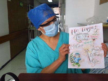 """ACOMPAÑA CRÓNICA: CORONAVIRUS MÉXICO - MEX3232. CIUDAD DE MÉXICO (MÉXICO), 28/06/2020.- Fotografía del 23 de junio donde se observa a María del Carmen Cedillo, encargada del área COVID y recuperación, donde muestra un dibujo de la paciente peruana Kelly Torres (fuera de cuadro), en el área de rehabilitación del Hospital Juárez de México (México). El Hospital Juárez de Ciudad de México ha ideado una terapia muy útil para la fase final de la recuperación de pacientes con la COVID-19: una serie de actividades como hacer dibujos o escuchar música para que los enfermos olviden la soledad del aislamiento y su mente vuelva a estar ocupada. """"Empezamos cuando nos trajeron para rehabilitación y nos dieron la opción de empezar a dibujar. Y nos ayuda mucho. Te despeja un poco la mente de tantos miedos, te relaja"""", explica desde su cama a Efe Kelly Torres, una peruana que reside con su familia en México, país que suma 212.802 casos y 26.381 muertos. EFE/ Miquel Muñoz MEJOR CALIDAD DISPONIBLE"""