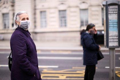 Una mujer con una máscara protectora espera en una parada de autobús en Londres, Gran Bretaña 22 de febrero de 2021. REUTERS/Hannah McKay