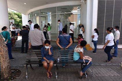 Personas son vistas afuera de un hospital en espera de informes de sus familiares que son atendidos por COVID-19.  EFE/Archivo