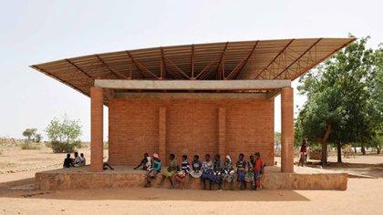 """Los edificios escolares de """"alta tecnología rural"""" que Francis Kéré ha construido en su pueblo natal de Gando, al sureste de la capital de Burkina Faso, Uagadugú, se erigen como una alternativa convincente y consciente del clima al acero, vidrio y aire acondicionado. Kéré diseñó la escuela primaria cuando era estudiante en Alemania, y encarna sus principios de bajo costo y baja energía (Kere Architecture)"""