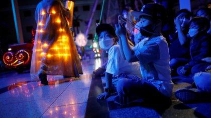 Niños surcoreanos llevan máscaras protectoras para evitar la propagación de la enfermedad coronavirus (COVID-19) mientras ven un desfile en un parque de atracciones en Seúl el 30 de abril de 2020 (REUTERS/Kim Hong-Ji)