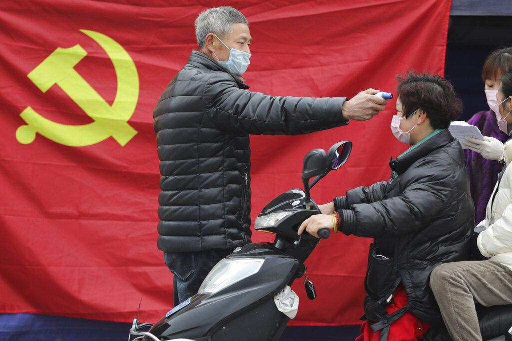 Un voluntario frente a una bandera del Partido Comunista le toma la temperatura a una persona que conduce una moto en un retén en Hangzhou, en la provincia oriental de Zhejiang (Chinatopix vía AP/archivo)