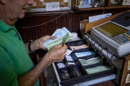 Una persona maneja una caja registradora en un local comercial con moneda venezolana y d�lares estadounidenses, el 24 de noviembre del 2020, en Caracas (Venezuela). EFE/Miguel Guti�rrez