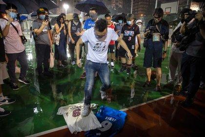 Un fanático chino pisotea una camiseta de LeBron James a modo de protesta en Hong Kong (AP)