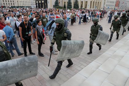 Miembros de las tropas del Ministerio del Interior de Bielorrusia caminan frente a una manifestación de la oposición contra la violencia policial cerca de la Casa de Gobierno en la Plaza de la Independencia en Minsk el 14 de agosto de 2020. (REUTERS/Vasily Fedosenko)