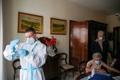 FILE PHOTO: A health worker prepares a dose of the Pfizer-BioNTech vaccine against the coronavirus disease (COVID-19), during home visits to carry out vaccinations, in Rome, Italy, March 17, 2021. REUTERS/Yara Nardi/File Photo