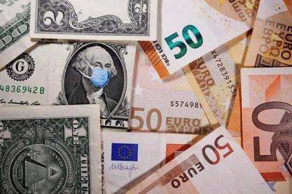 Ilustración fotográfica que muestra la imagen de George Washington con una mascarilla en un billete de dólar junto a billetes de euro. 31 marzo 2020. REUTERS/Dado Ruvic