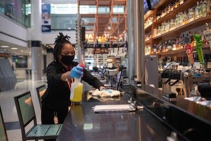 Una mujer limpia y desinfecta un restaurante de la Terminal E del Aeropuerto Intercontinental George Bush de IAH en medio del brote de la enfermedad coronavirus en Houston, Texas (Reuters)
