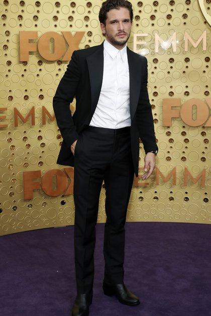 Kit Harington, el protagonista de Game of Thrones se lució en la alfombra violeta con un esmoquin de saco, camisa y pantalón, sin corbata ni moño y completó su look con zapatos de cuero