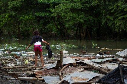 Una mujer camina por encima de los restos de su hogar (AFP)