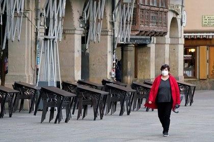 Una mujer con mascarilla camina frente a la terraza de un bar cerrado tras las restricciones al movimiento impuestas por la Diputación Foral de Navarra para tratar de contener la propagación de la COVID-19, en Pamplona, Navarar, España, el 22 de octubre de 2020. REUTERS/Vincent West
