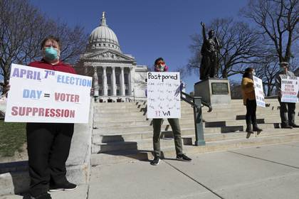 Un grupo de manifestantes protesta frente al Capitolio de Wisconsin por la decisión de las autoridades de llevar a cabo elecciones primarias a pesar de la pandemia del coronavirus (Amber Arnold/Wisconsin State Journal vía AP)