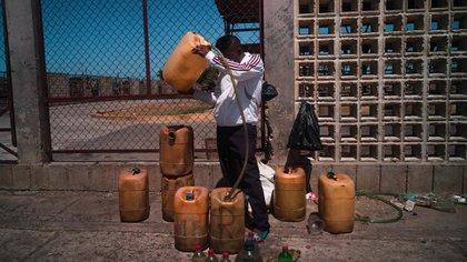 Un hombre vende gasolina en una parada de buses en Paraguaipoa, Venezuela. Como una cruel ironía para la Venezuela petrolera, el poco combustible que hay llega desde Colombia.
