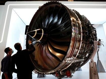 Personal de Rolls Royces usando mascarilla mientras inspeccionan un motor turboventilador de uso aeronáutico