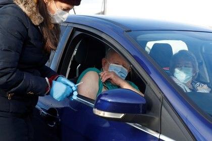 Un hombre recibe la vacuna Pfizer-BioNTech COVID-19 desde su automóvil en un centro de vacunación en medio del brote de la COVID-19 en Hyde, Gran Bretaña (Reuters)