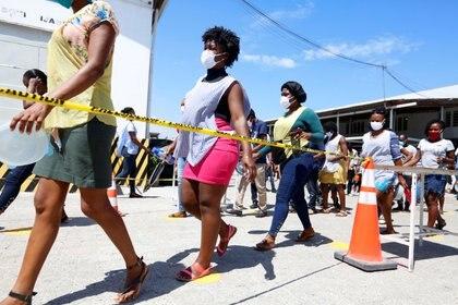 Trabajadores caminan a una distancia segura entre ellos durante un descanso en una fabrica local de ropa que produce máscaras protectoras en Puerto Príncipe, Haití, el 21 de abril de 2020. (REUTERS/Jeanty Junior Augustin)