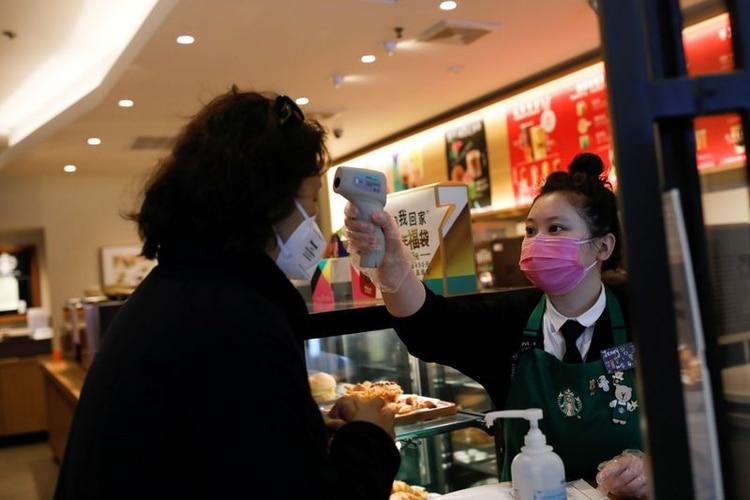 FOTO DE ARCHIVO. Una trabajadora usa un termómetro para chequear la temperatura de una cliente que entra a una tienda de Starbucks, mientras el país es golpeado por un nuevo coronavirus, en Pekín, China. 30 de enero de 2020. REUTERS/Carlos Garcia Rawlins.