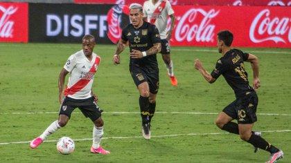 De La Cruz, otro de los destacados de River, maneja la pelota ante dos rivales de Racing (Télam)