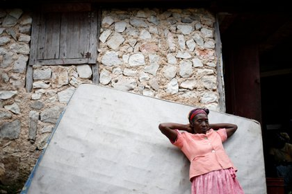 Una mujer se apoya en un colchón de la cama de un vecino que regresó después de años de vivir en República Dominicana, en Boucan Ferdinand, Haití, 10 de octubre de 2018.
