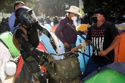 Un agricultor se pelea con un miembro de la Guardia Nacional de México durante una protesta contra la decisión del gobierno de desviar el agua de la represa La Boquilla a los Estados Unidos, como parte de un tratado bilateral de agua de 1944 entre los dos países, en Camargo, del estado Chihuahua, México. 8 de septiembre de 2020. REUTERS/Jose Luis Gonzalez