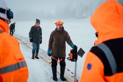 Janne Käpylehto (C) da instrucciones sobre cómo cortar el hielo para realizar el carrusel de hielo. (Alessandro RAMPAZZO / AFP)