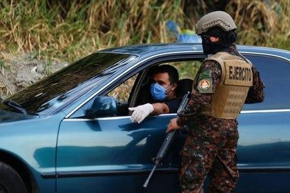 Un hombre usa cubrebocas y guantes en un punto de control del Ejército en medio de la cuarentena domiciliaria obligatoria en El Salvador. 29 de marzo de 2020.  REUTERS/Jose Cabezas