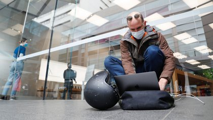 Un cliente usa su portátil mientras espera en la cola de la tienda de Apple en el suburbio de Bondi Junction de Sydney