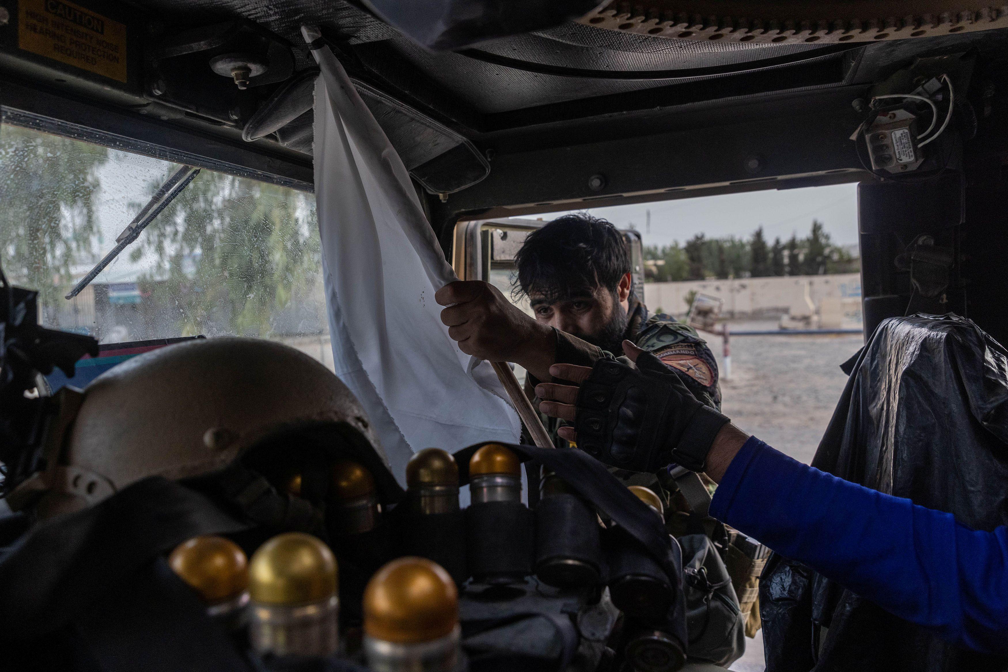 Un miembro de las fuerzas especiales afganas confisca una bandera talibán montada en un árbol durante la misión de rescate de un oficial de policía asediado en un puesto de control rodeado por los talibanes, en la provincia de Kandahar, Afganistán, 13 de julio de 2021.